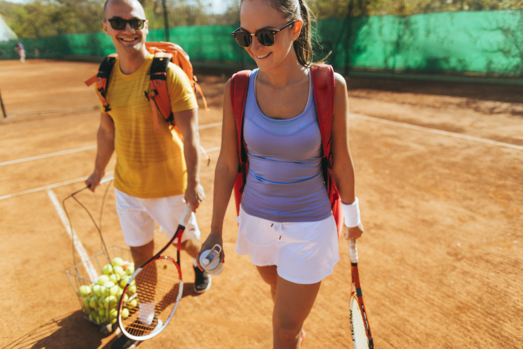 Young couple of tennis players after the match